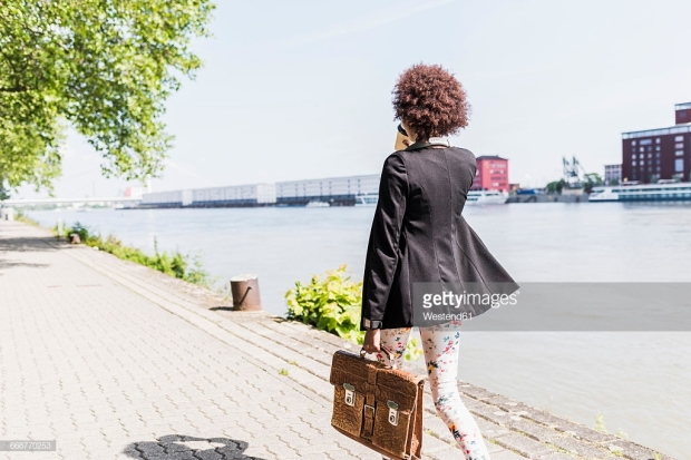 germany-mannheim-back-view-of-young-businesswoman-with-briefcase-and-picture-id668770253